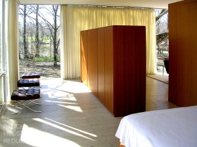 Farnsworth House by Mies van der Rohe - Bedroom with custom plywood built in closet dividing changing area from living area